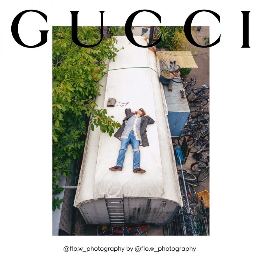 Florian Witte rests on top of a metal building for Gucci's fall 2020 campaign.