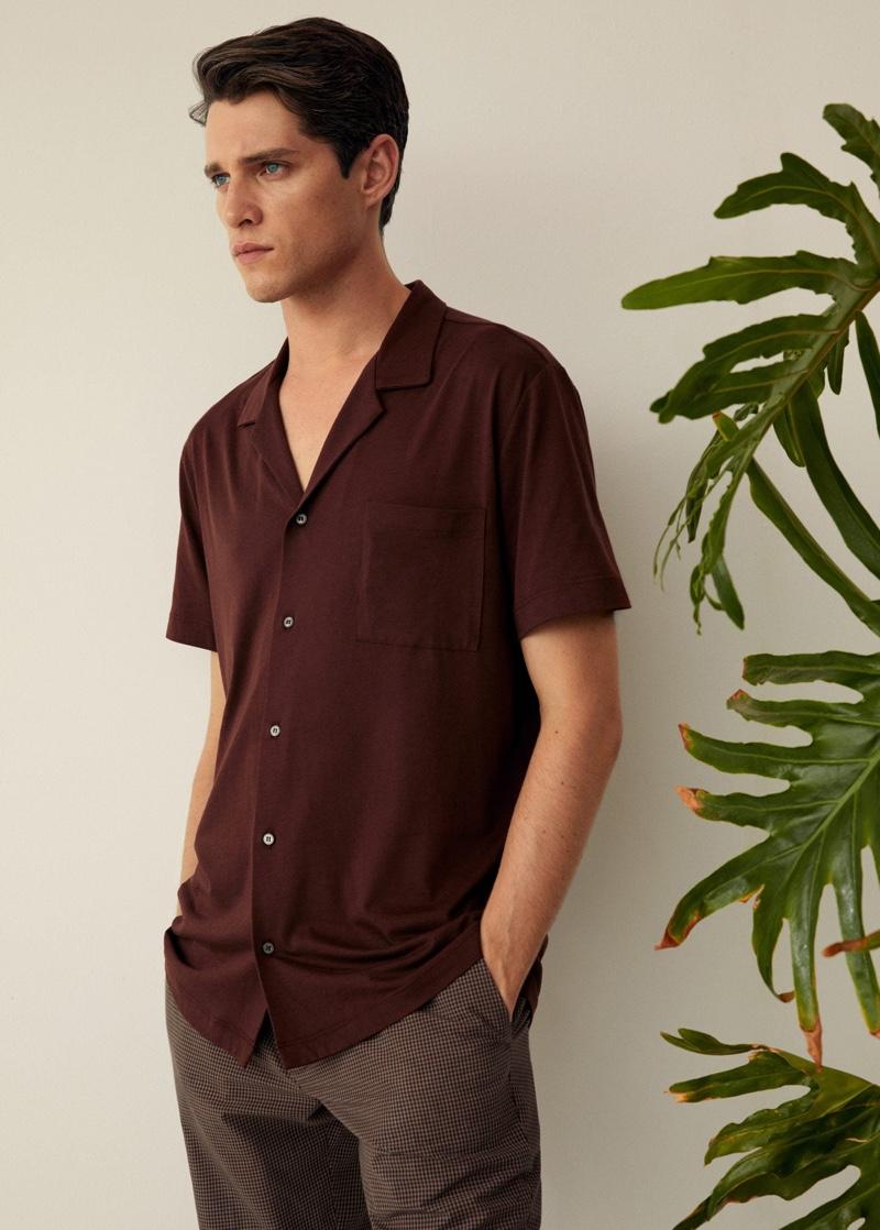 Donning Mango, Luke Powell wears a cotton knit shirt.