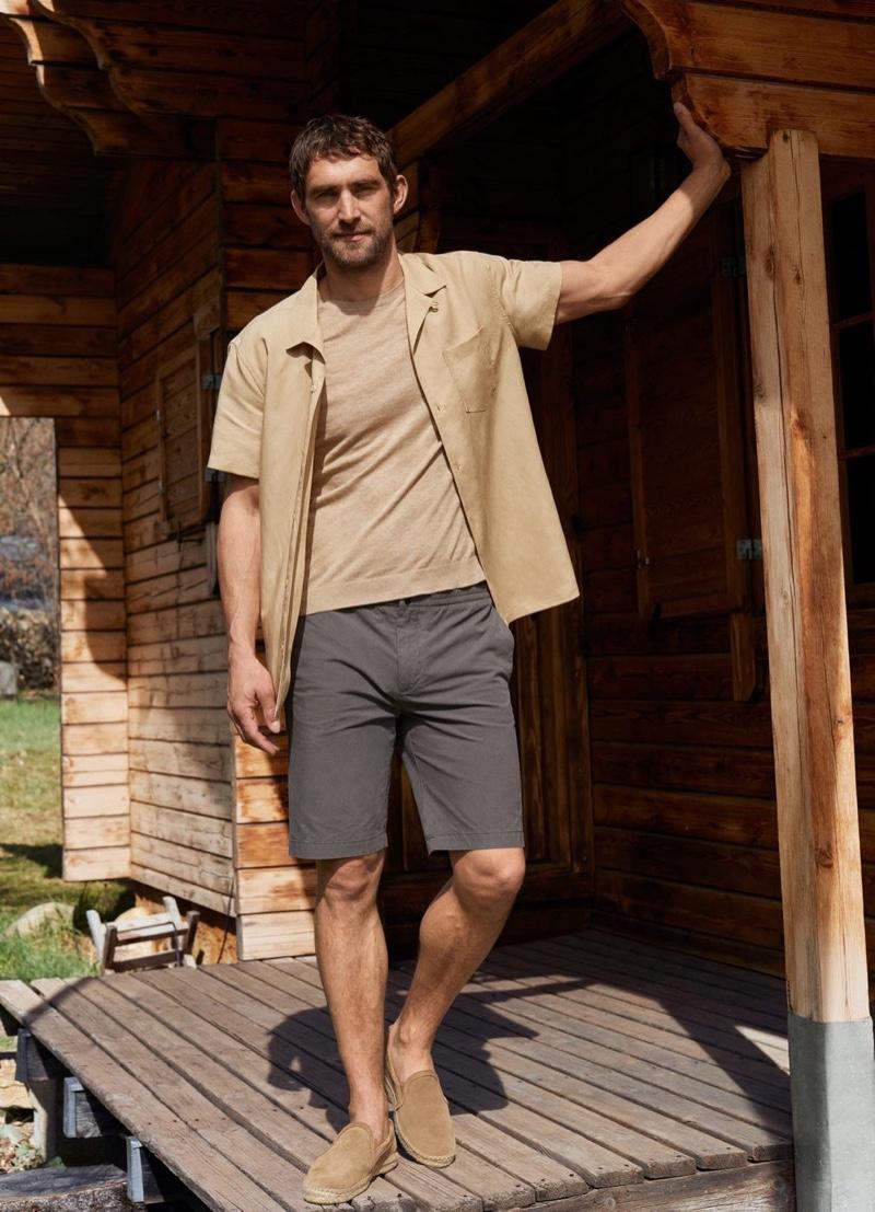 British model Will Chalker dons a Mango linen-blend short-sleeve shirt with elastic waist cotton Bermuda shorts.