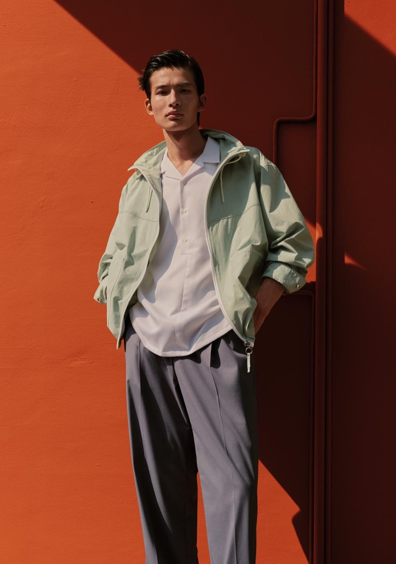 Front and center, Huang Shixin sports a Zara contrasting zipper jacket, textured polo shirt, and pleated suit pants.
