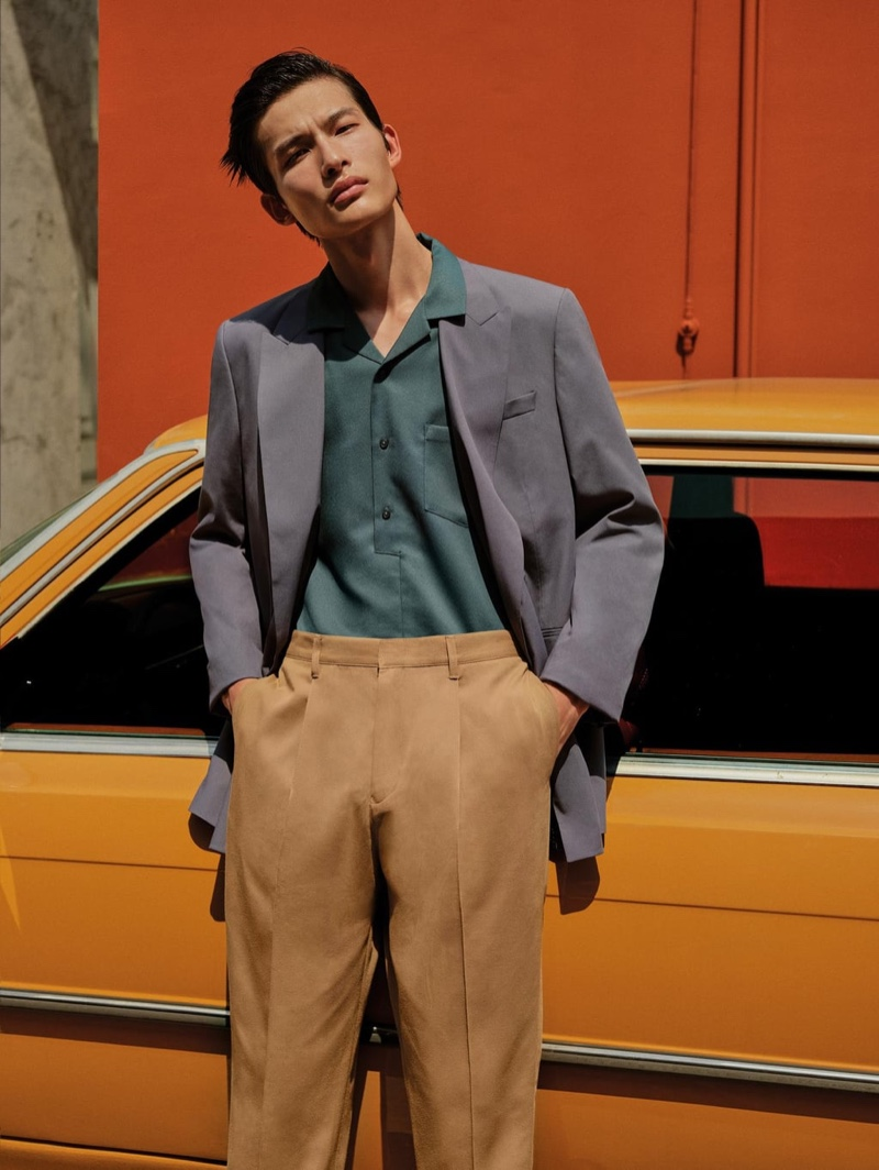 Model Huang Shixin wears a double-breasted suit jacket, textured polo shirt, and cropped pleated chino pants from Zara.