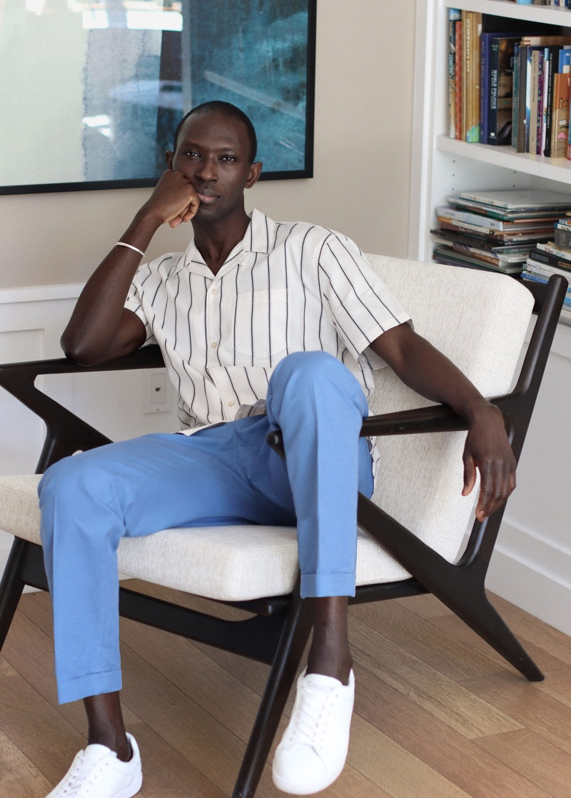 Reuniting with Mango for summer, Armando Cabral models a striped shirt with pleated trousers.