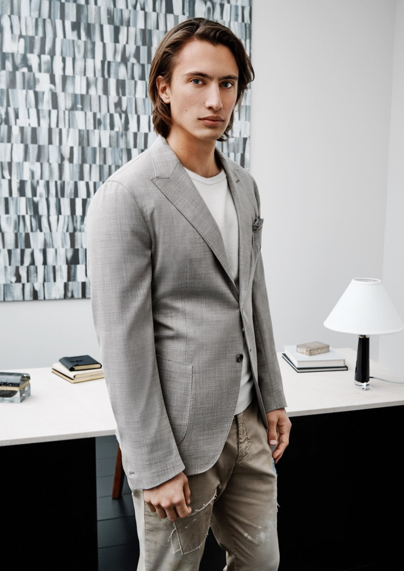 James Turlington dons a linen and wool jacket with a sweater and distressed pants from Eleventy.
