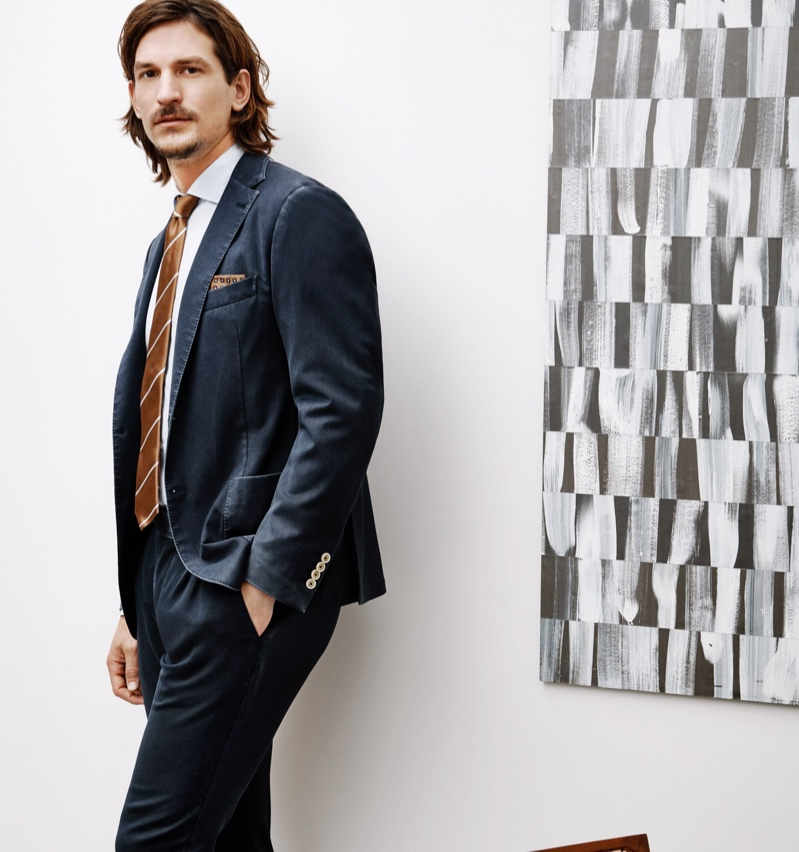 An elegant vision, Jarrod Scott wears a wool suit jacket and pants with a cotton shirt by Eleventy.