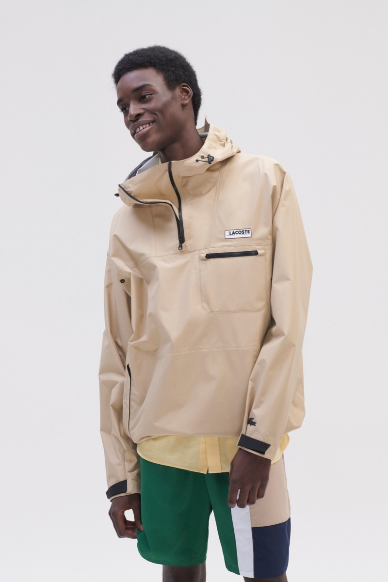 Model Babacar N'doye dons a windbreaker, color-blocked pants, and a yellow shirt from Lacoste.