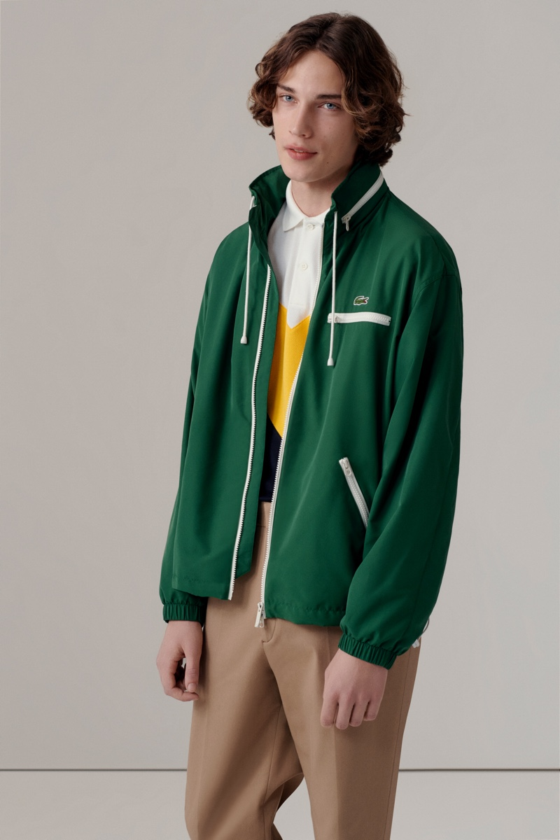 Freek Iven dons a green jacket with a colorblocked polo and pleated khaki pants from Lacoste's fall-winter 2020 collection.