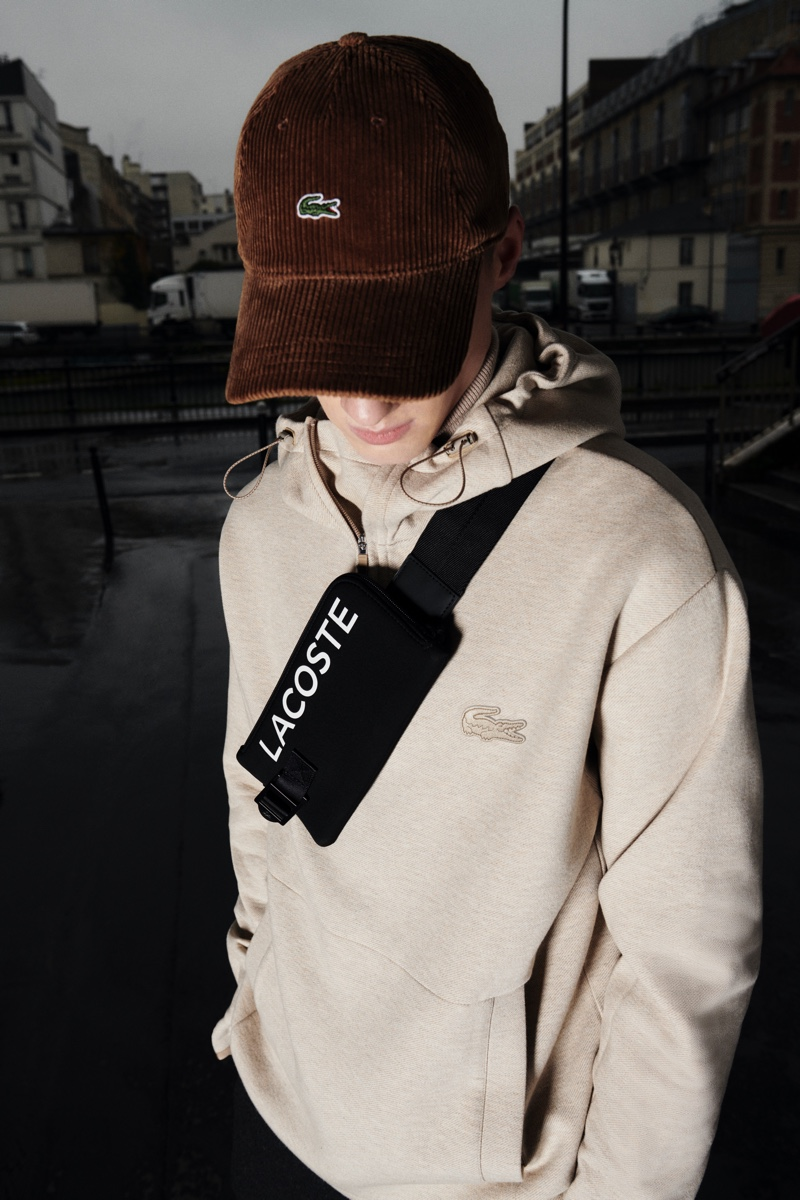 Braien Vaiksaar goes casual in a Lacoste hoodie, corduroy cap, and belt bag from the brand's fall-winter 2020 collection.