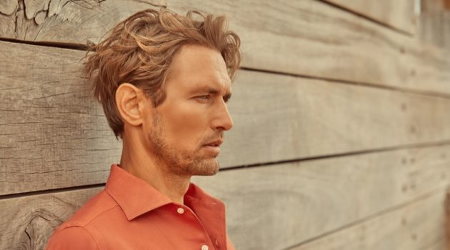 Delivering a side profile, Robertas Aukstuolis dons a coral Portofino linen shirt for Luca Faloni's high summer 2020 campaign.
