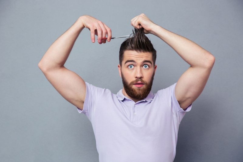 Man Cutting His Own Hair with Scissors