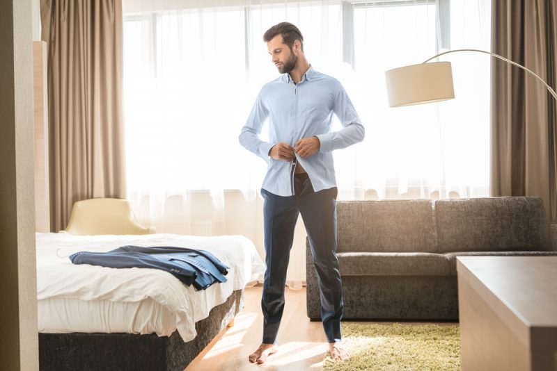 Man Putting on Dress Shirt and Suit
