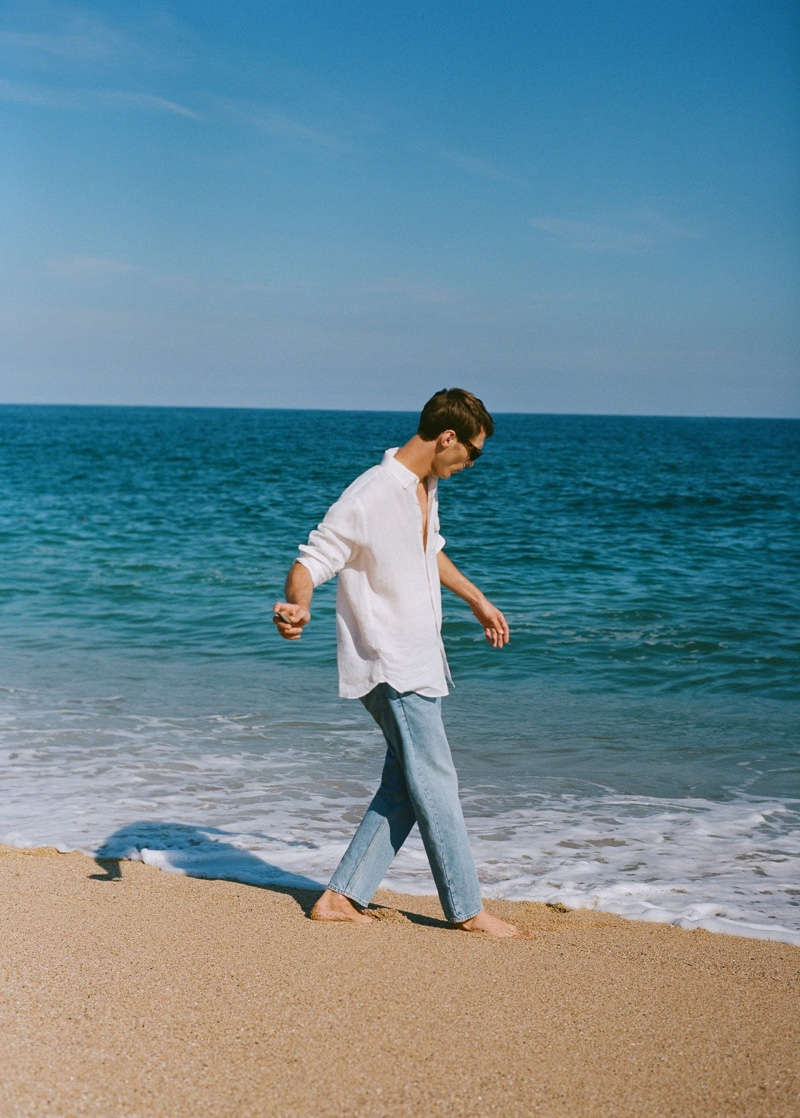 Taking to the beach, Clément Chabernaud dons a 100% linen shirt with Mango's light wash jeans.