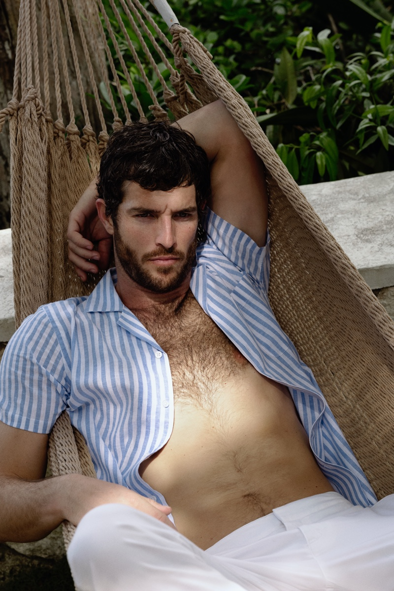 Relaxing, Justice Joslin wears a Thunderball stripe shirt from Orlebar Brown's 007 Heritage collection.