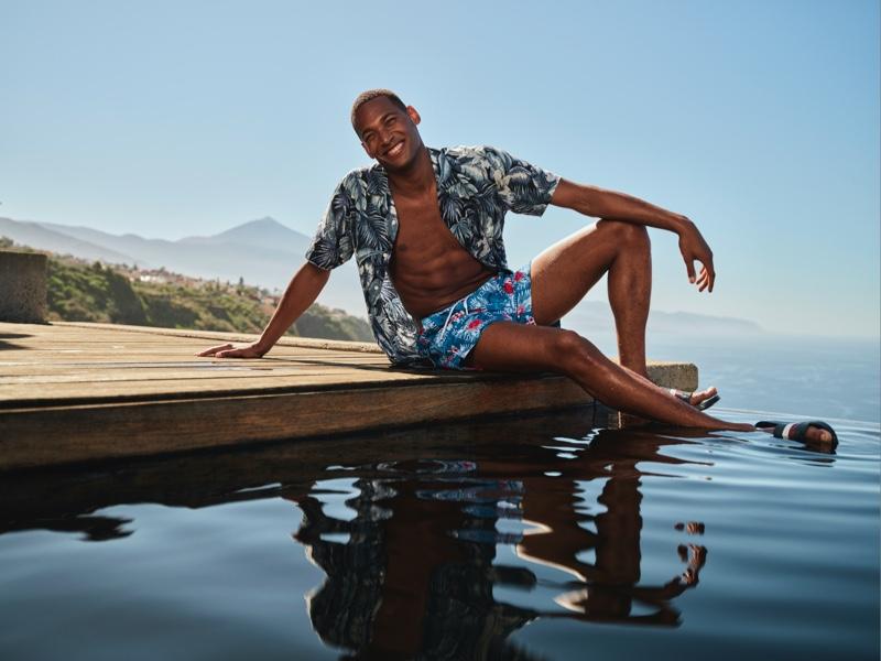 Patrick Nodanche sports blue recycled botanical swim trunks from Tommy Hilfiger.