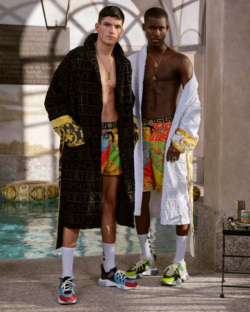 Models Islam Dulatov and Ismael Savane sport custom robes with swimwear from Versace's summer capsule collection.