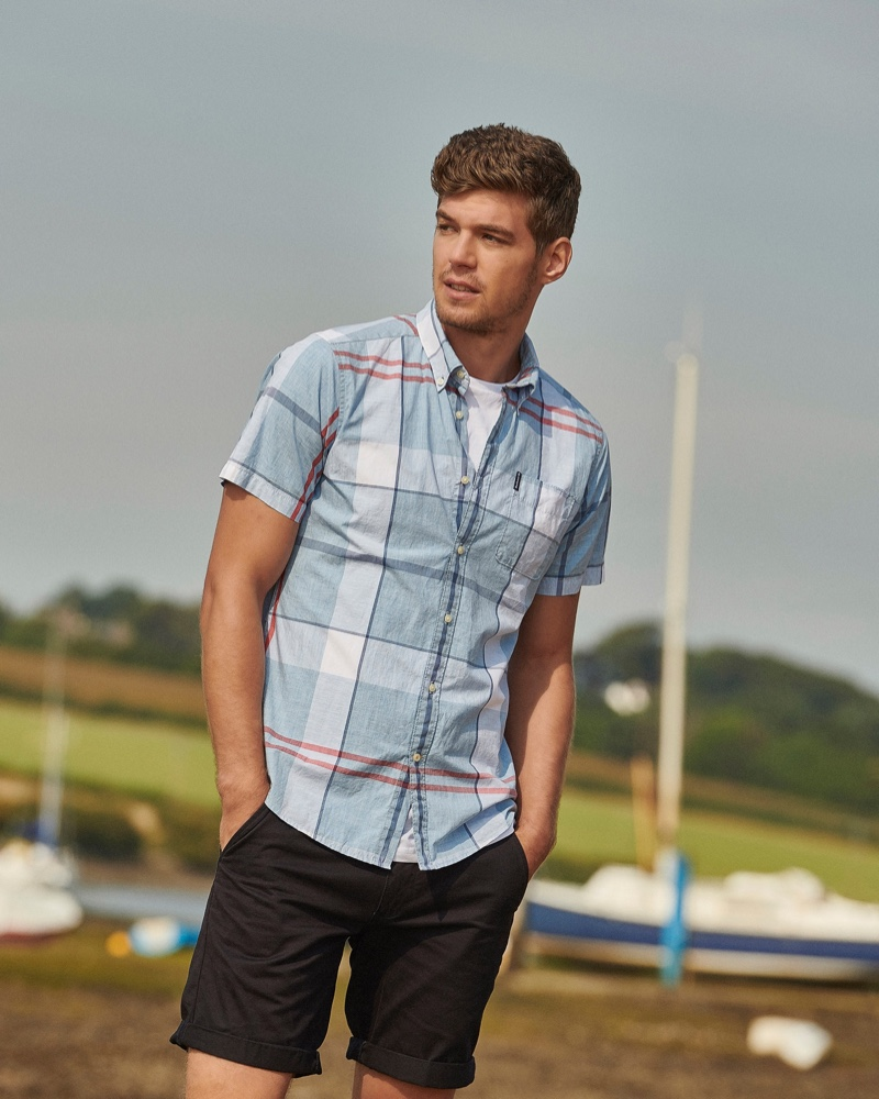 Front and center, Bertold Zahoran models a tartan short-sleeve shirt with cuffed shorts by Barbour.