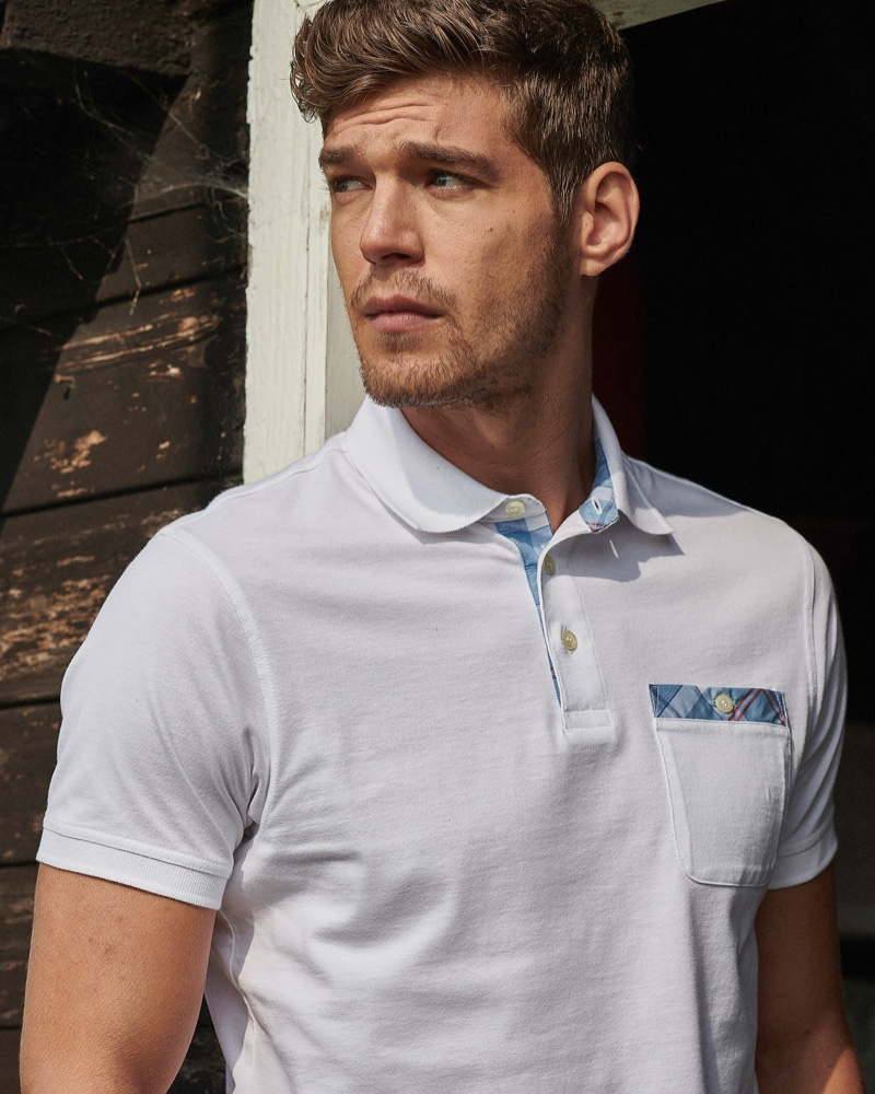 Model Bertold Zahoran dons a tartan trimmed polo from Barbour.