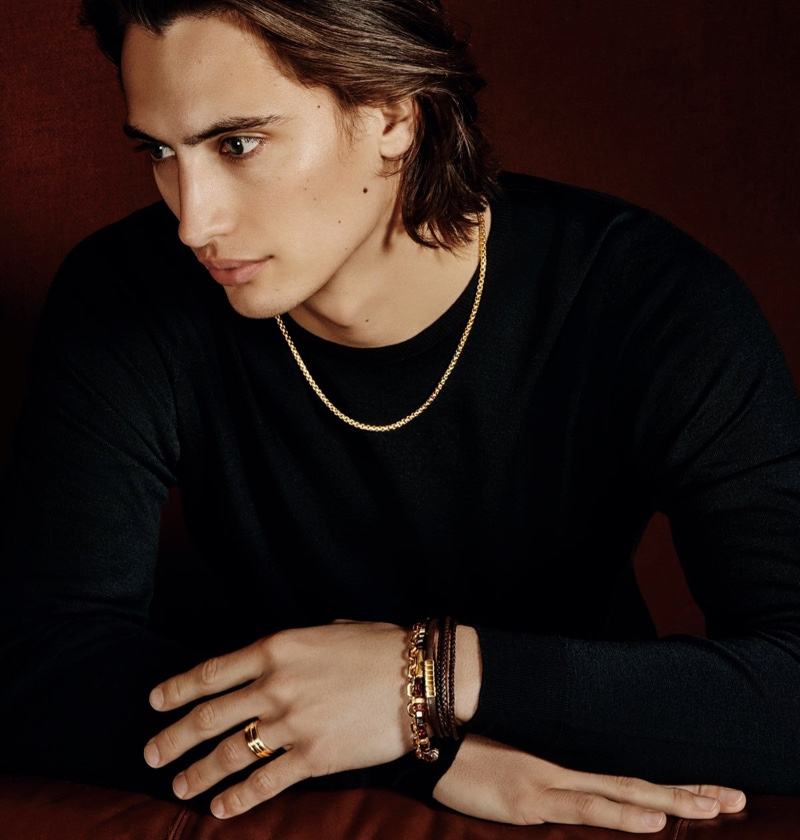 James Turlington dons a David Yurman box chain 18k gold necklace with a chevron triple-wrap leather bracelet with silver and southwest leather bracelet with 18k gold. He also models the label's Hex 18k gold spiritual bead bracelet, chain 18k gold bracelet, and deco 18k gold band ring.