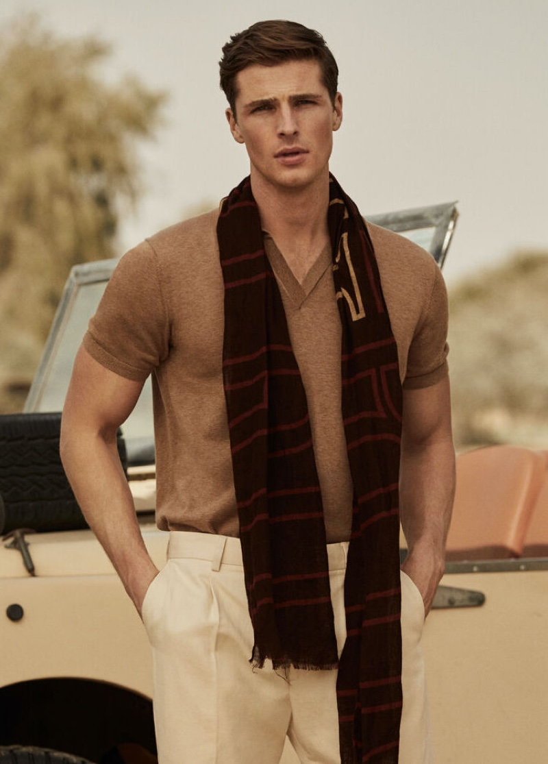 Edward Wilding models a short-sleeve tricot polo shirt with Pima cotton chinos and a printed logo scarf from Pedro del Hierro.