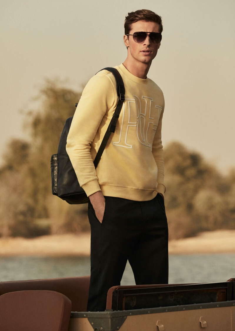 Playing it smart casual, Edward Wilding models a crewneck sweatshirt with a leather logo backpack, drawstring trousers, and aviator sunglasses by Pedro del Hierro.