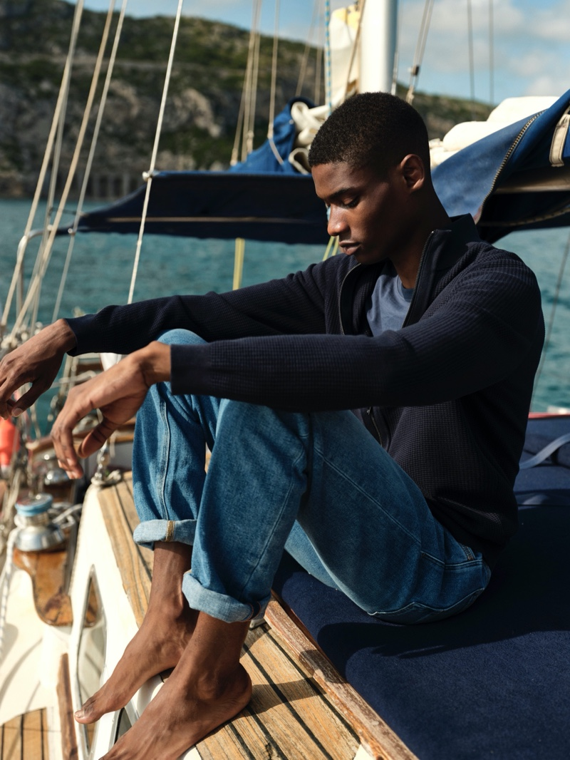 Enjoying a quiet moment, Rachide Embalo models a cashmere cardigan with a linen t-shirt and stone wash jeans from Massimo Dutti.
