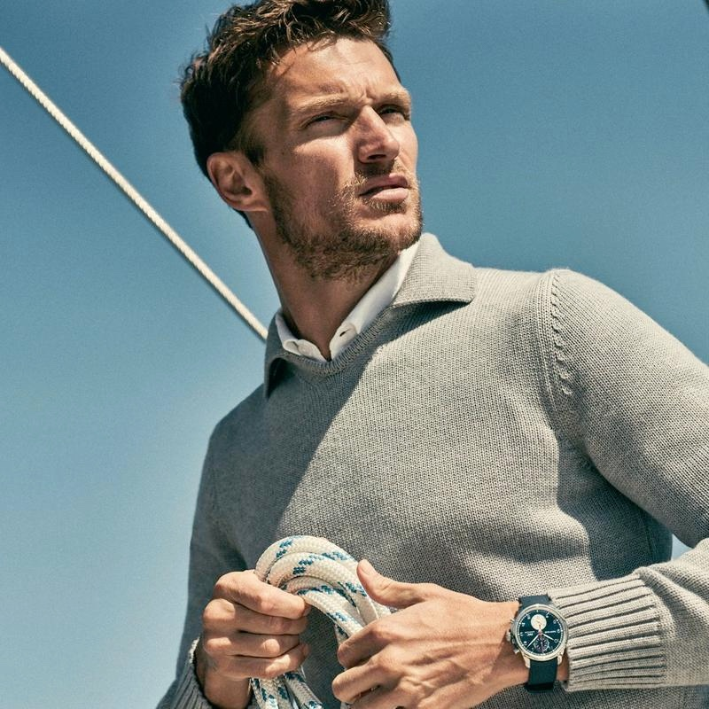 Embracing nautical style, Shaun Dewet wears a grey merino sweater from Orlebar Brown's IWC collection.