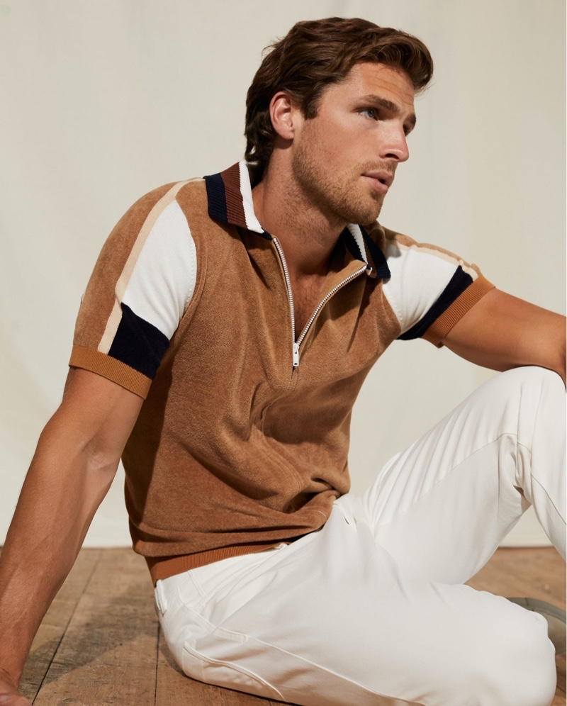 Channeling a retro ease, Edward Wilding models a toweling zip through polo shirt by Reiss.
