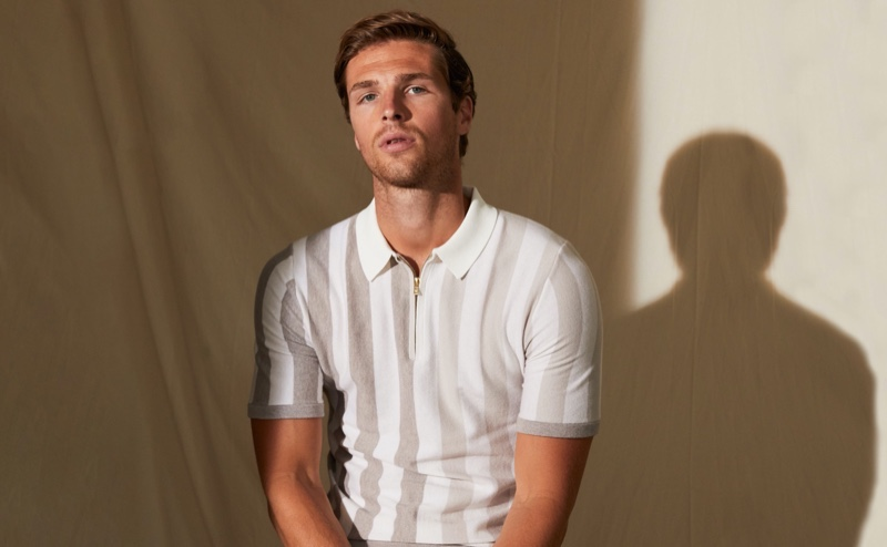 Edward Wilding dons a striped zip neck polo shirt from Reiss.