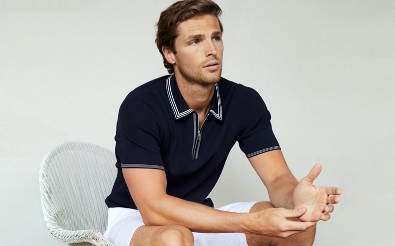 Donning a look that's ideal for tennis, Edward Wilding sports a tipped zip neck polo shirt in navy with Reiss' Wicket shorts.