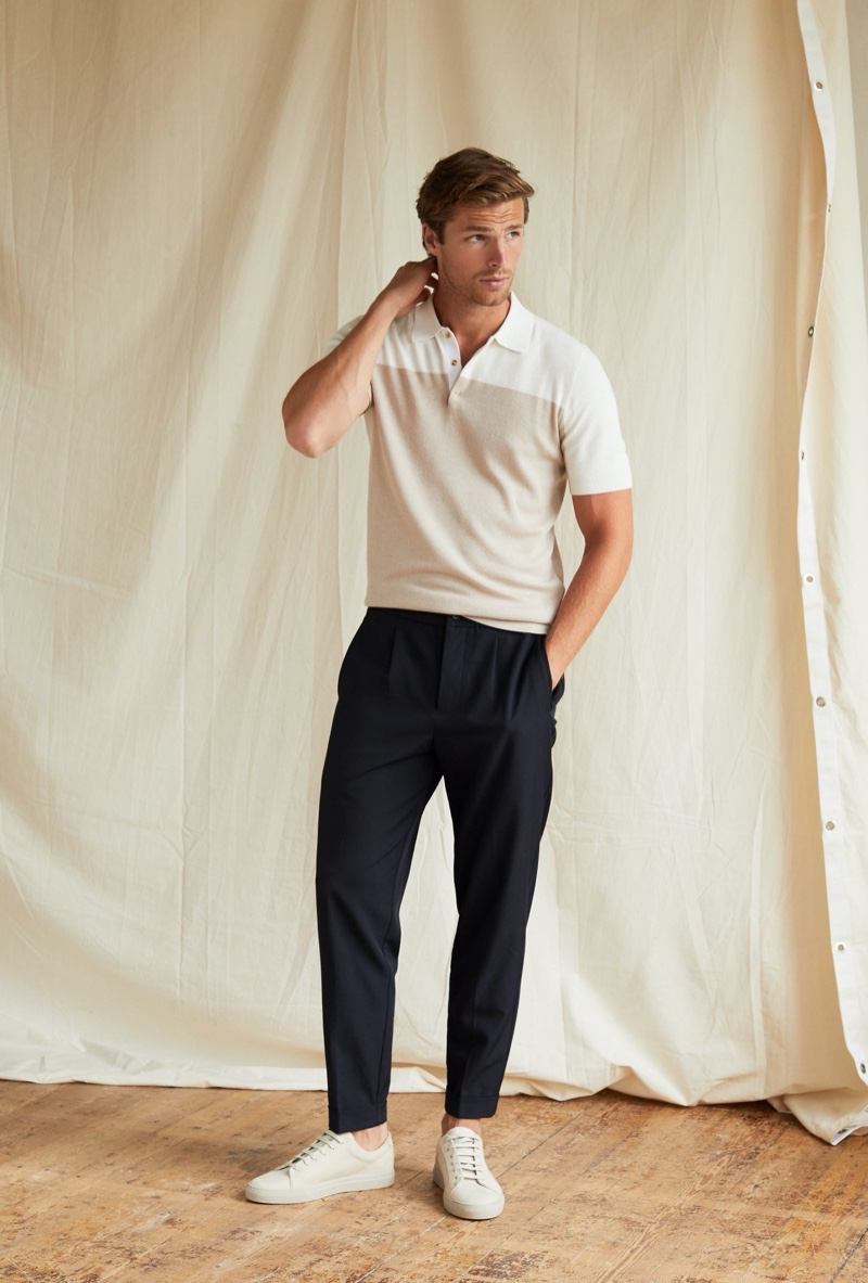 Front and center, Edward Wilding wears a color-block polo shirt with Reiss pleat front trousers in navy.