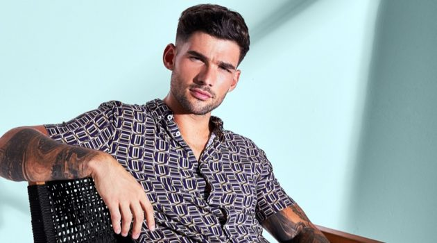 Brandan Stevens sports a short-sleeve printed shirt with ripped jeans from River Island.