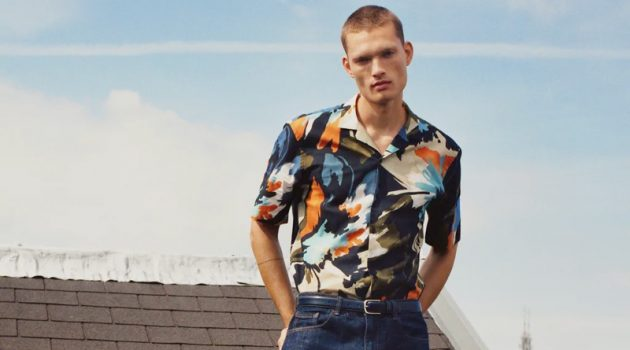 Taking to a rooftop in Amsterdam, William Los sports a graphic print short-sleeve shirt with classic blue denim jeans by Zara.
