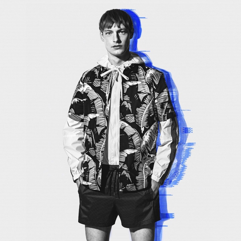 Roberto Sipo sports a printed short-sleeve shirt with a hooded pullover and shorts by Antony Morato.