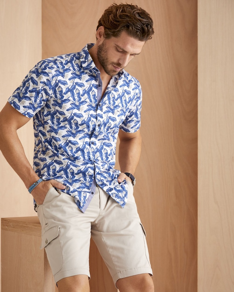 Model Simone Bredariol sports a printed short-sleeve shirt with cargo shorts from BRAX's summer 2020 collection.