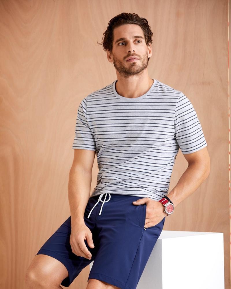 Showcasing summer style, Simone Bredariol wears a striped t-shirt with drawstring shorts by BRAX.