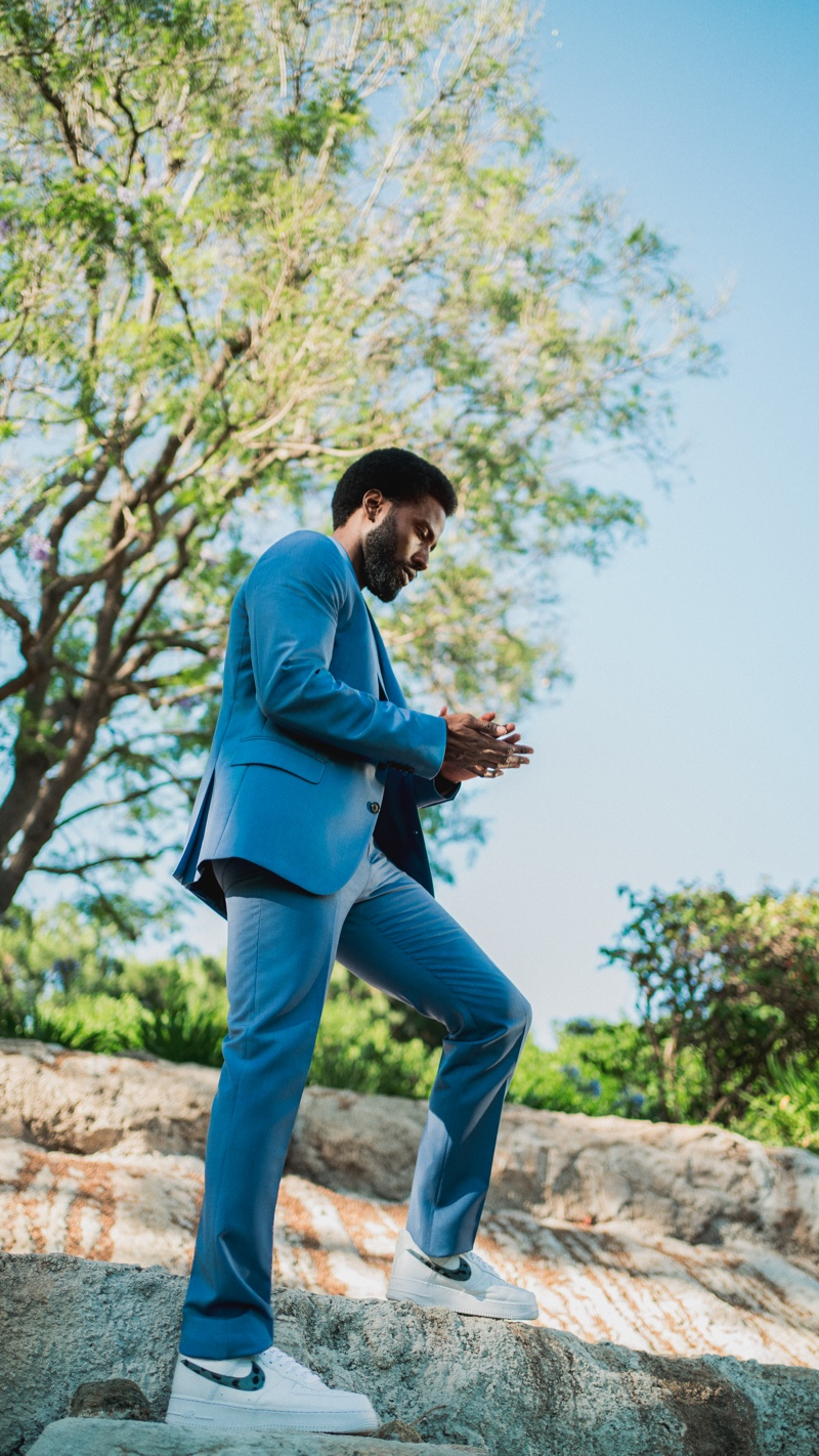 Stepping outdoors, John David Washington sports a Paul Smith suit with a Save Khaki United t-shirt and Nike sneakers.