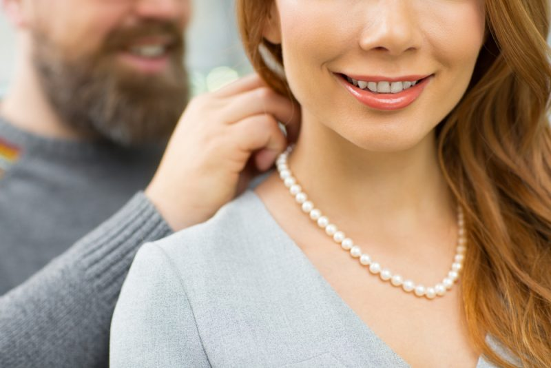 Man Putting Pearl Necklace on Woman