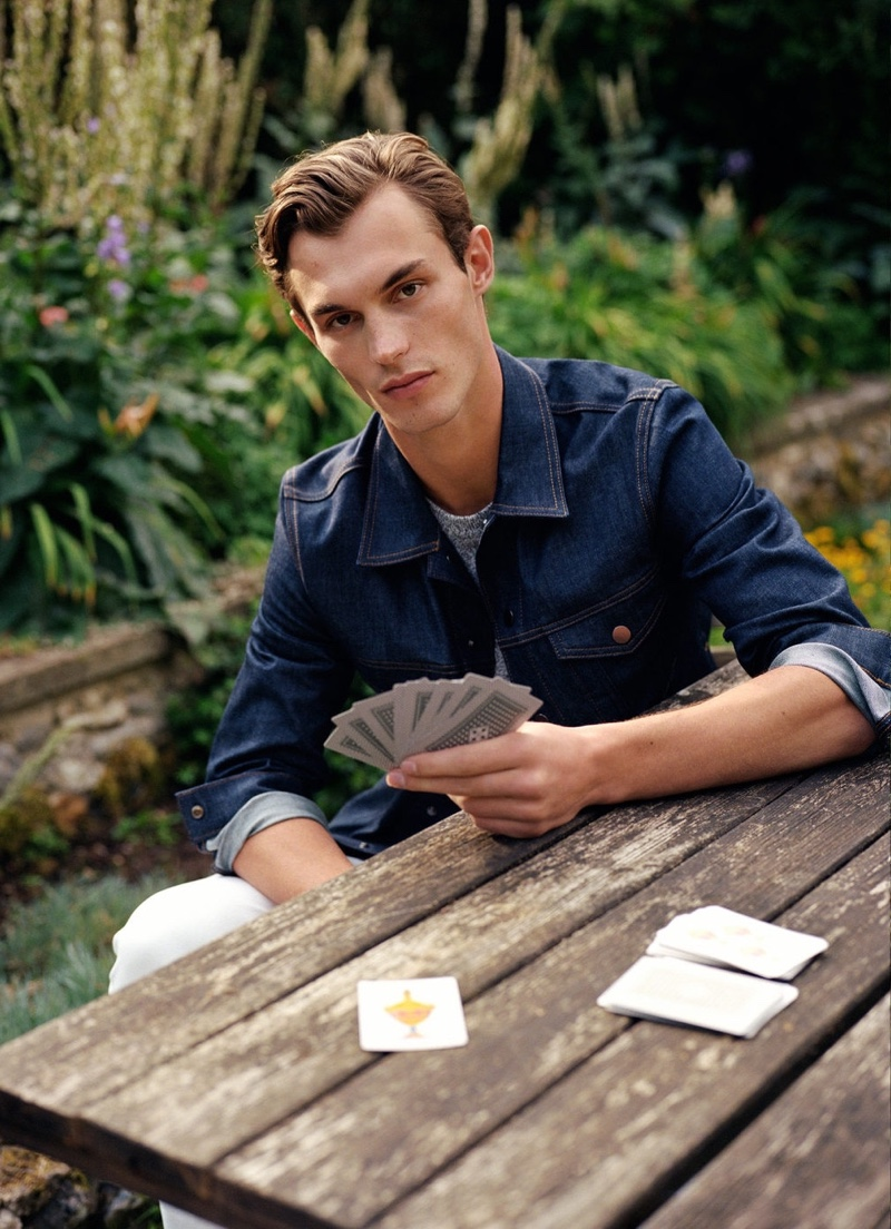 Playing cards, Kit Butler wears a dark wash jean jacket from Mango Man.