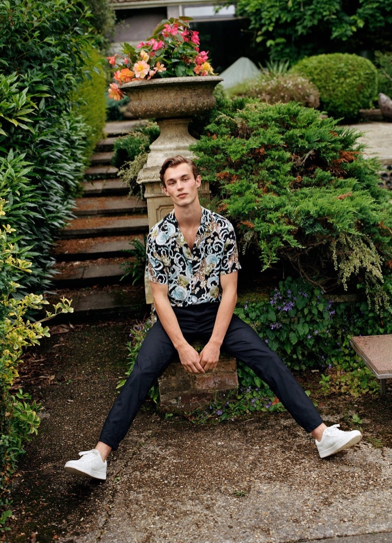 Kit Butler models a short-sleeve printed shirt with smart pants from Mango.