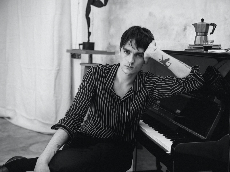 Posing against a piano, Alain-Fabien Delon sports a striped shirt with trousers from Mango Man.