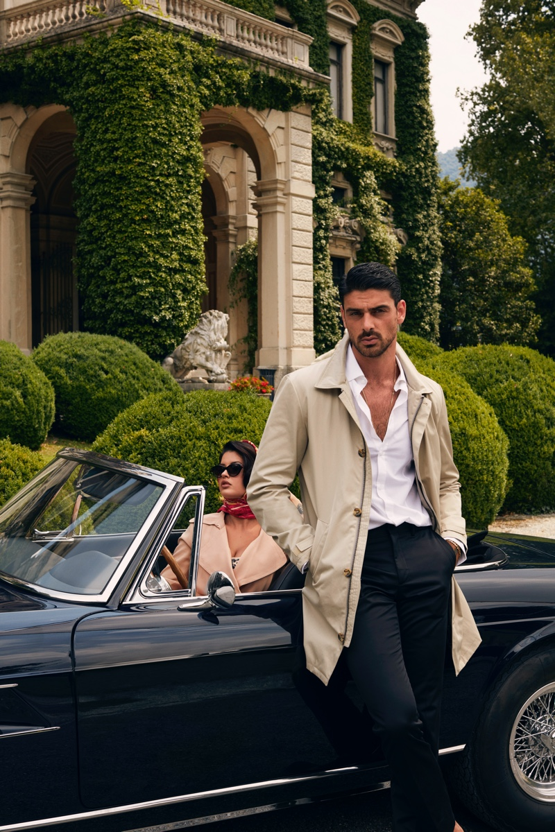 Michele Morrone dons a smart trench, white shirt, and trousers for GUESS' fall-winter 2020 campaign.