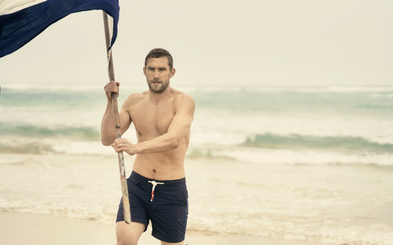 Will Chalker sports Orlebar Brown's Standard navy mid-length swim shorts.