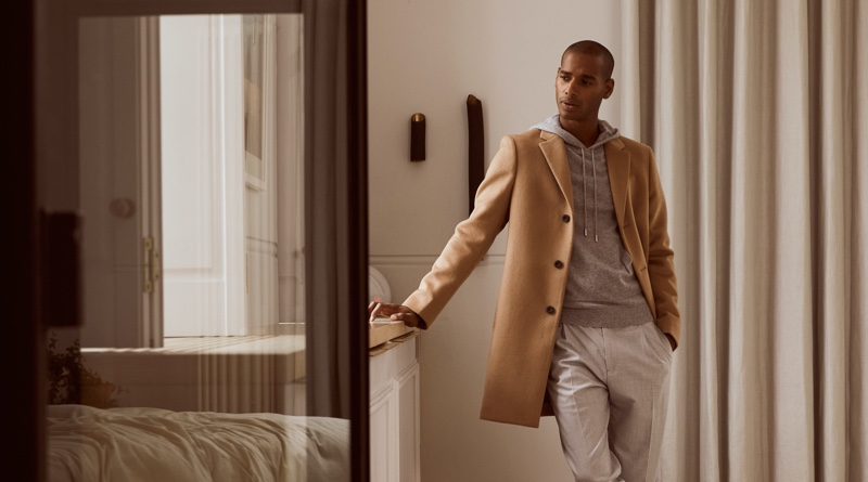 Sacha M'Baye dons a Reiss Gable coat with the brand's Santiago hoodie and Brighton trousers.