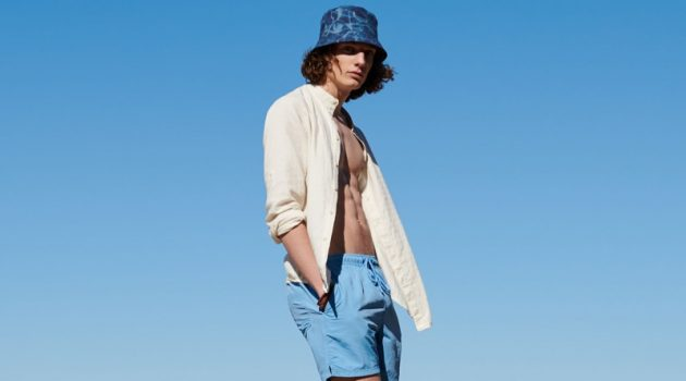 Sporting a bucket hat with a yellow top and blue swim shorts, Pawel Feledyn wears Reserved.