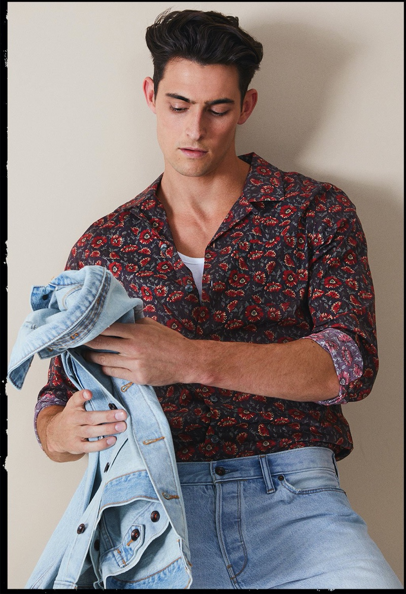 Donning light wash denim, Rhys Pickering makes a statement in Todd Snyder's Liberty camp collar long-sleeve shirt in brick floral print.