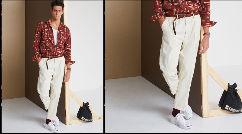 Front and center, Rhys Pickering models Todd Snyder's Liberty camp collar long-sleeve shirt in feather print with The Pleated Pant in ivory coast.
