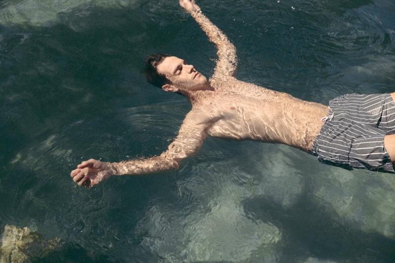 Swimming, Vincent Lacrocq wears gray striped swim shorts by Zara.