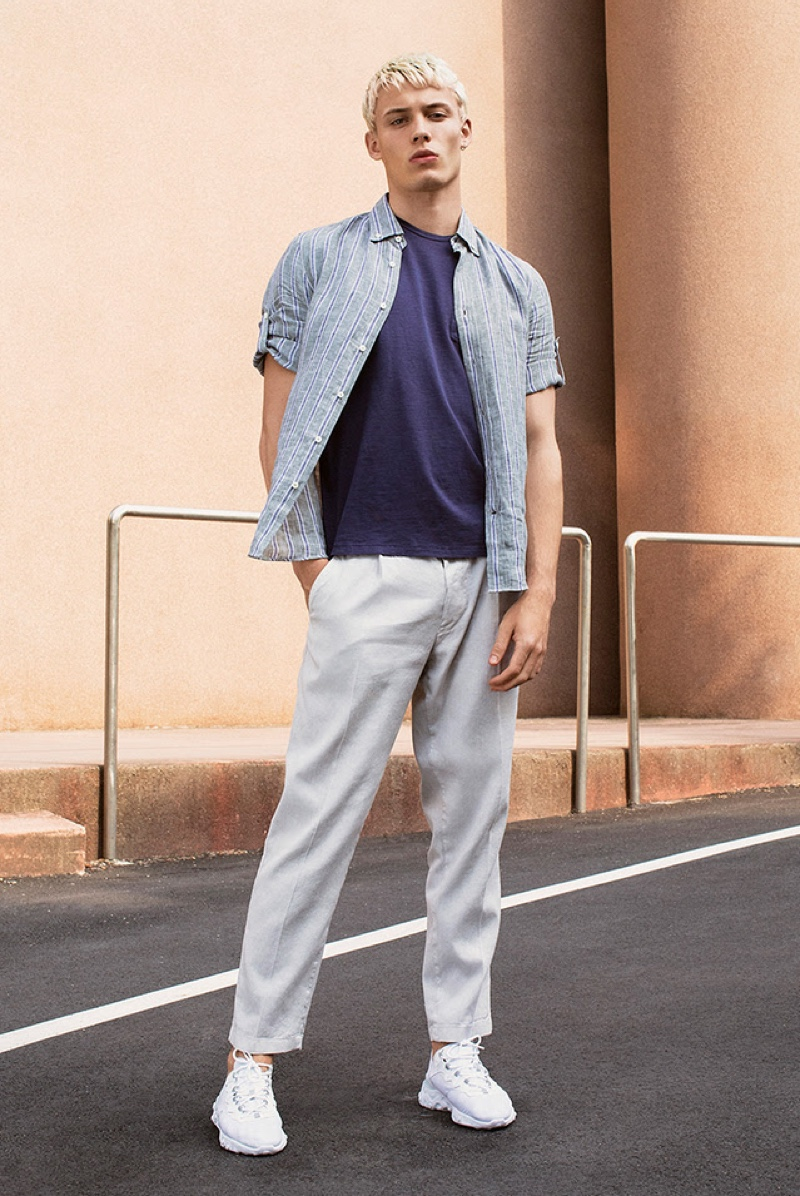 Front and center, João Knorr wears a striped shirt with a relaxed tee and pants from YOOX.