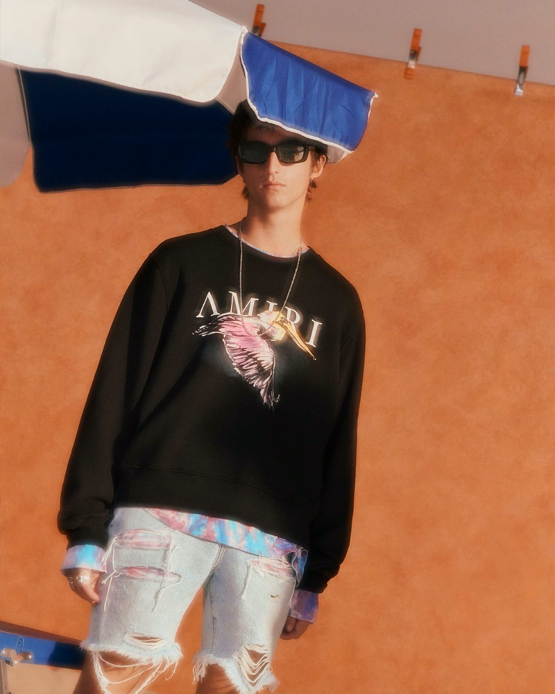 A cool vision, Alexander Carey Morgan wears an AMIRI printed loopback cotton-jersey sweatshirt, tie-dyed cotton-jersey t-shirt, and thrasher paneled distressed denim shorts.