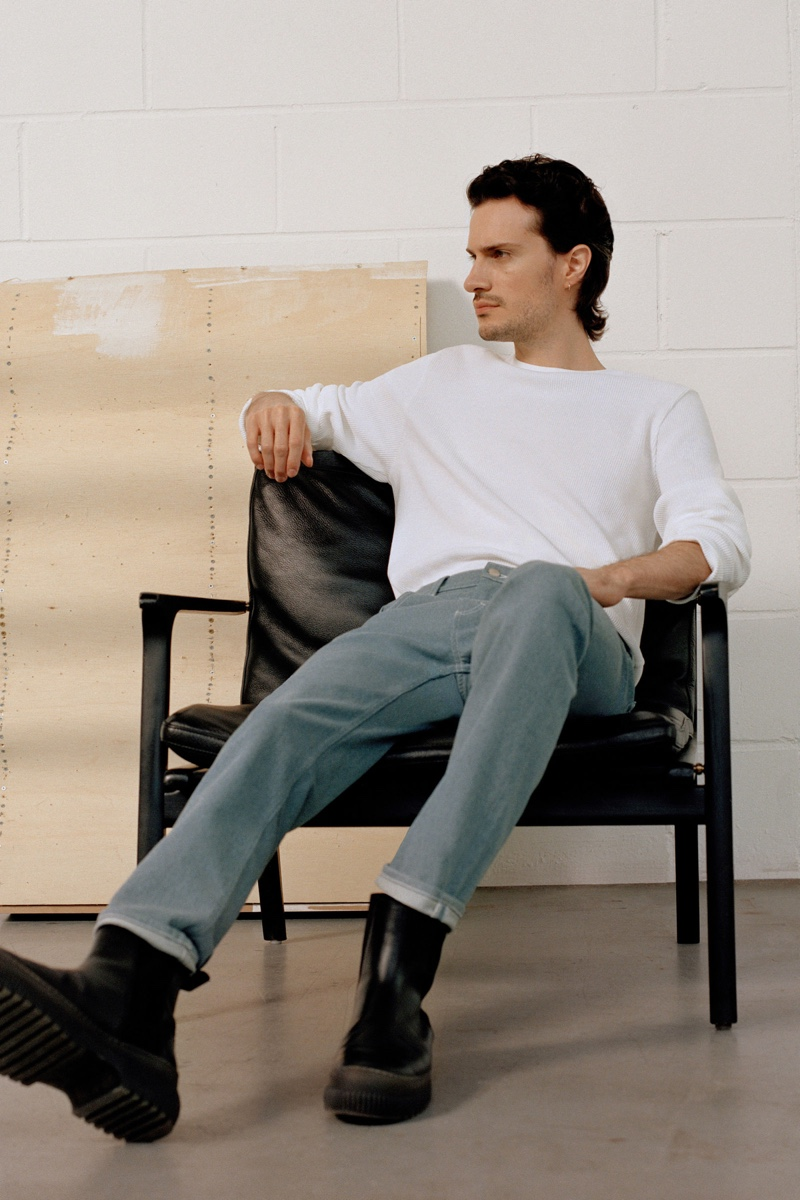 Relaxing, Tristan Pigott sports a COS ribbed pullover with recycled cotton slim-leg jeans.