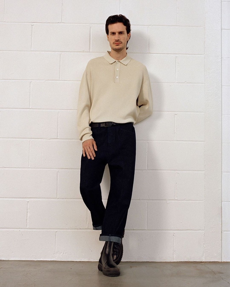 Front and center, artist Tristan Pigott wears a long-sleeve knit polo with sustainable denim jeans and chunky leather boots from COS.